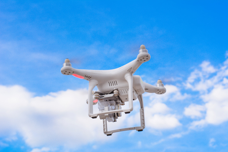 White drone, quadrocopter with photo camera flying concept on the sky. Stock Photo