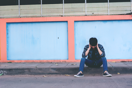 sitting on the ground: Lonely man sitting on the street Stock Photo