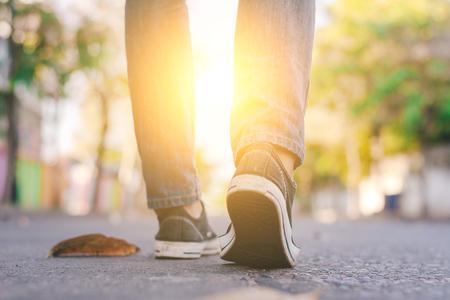 Uomo che indossa sneaker e jeans che camminano lungo la strada della città. Archivio Fotografico - 78621790
