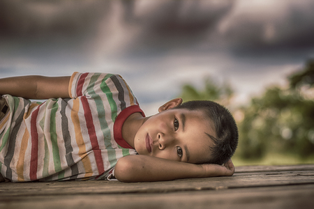 Little boy unhappy sleeping alone on abandoned temporary housing. Stock Photo