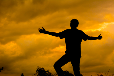 Silhouette man praying with hand up to God. Sunset background.