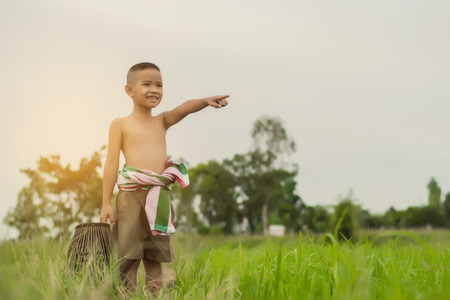 Asian boy to fish during the holidays in green farm field in summertime., Thailand.