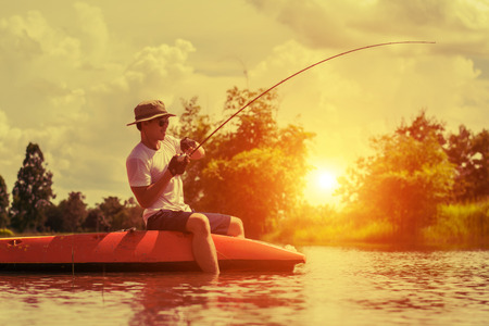 lost lake: fishing man on board into the river against the background of a picturesque landscape at dawn, on sunset.