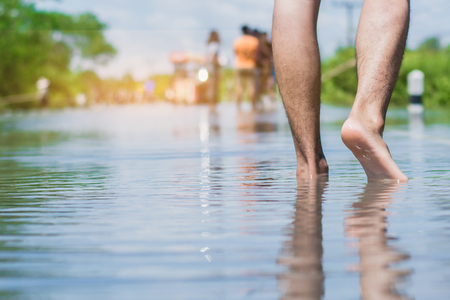 young man walks through the flood with his bare feet. Stock Photo