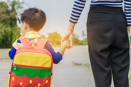 Mama houdt hand van kleine zoon met rugzak buitenshuis, terug naar school, naar huis terugkijken met overstromingen. Stockfoto