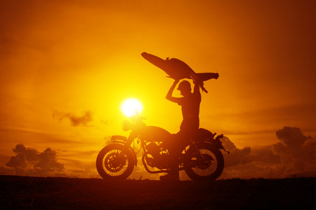 Silhouette of biker man with his motorbike beside the natural lake and beautiful, enjoying freedom and active lifestyle, having fun on a bikers tour.sunset background and sky. 免版税图像