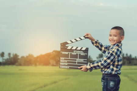 Kid playing film clapper board against summer sky background. Film director concept.
