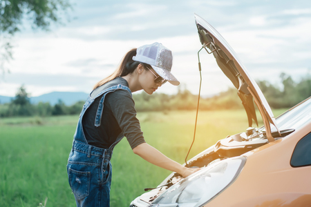 Hopeless young woman standing next to the broken car looking at the engine.