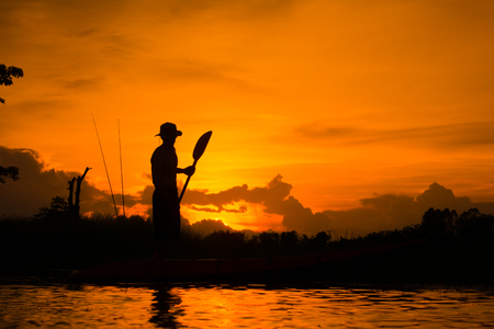 Silhouette of  fisherman standing on boat,hold paddle,on sunset background. Stock Photo