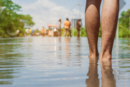 young man walks through the flood with his bare feet. Stok Fotoğraf