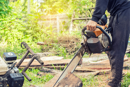 Man cutting wood with a chainsaw. Stock Photo