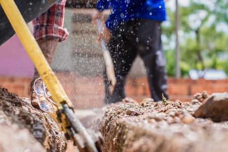 Trabajador de la construcción, la reparación de una tubería de agua rota en el camino de hormigón. Foto de archivo - 87406962