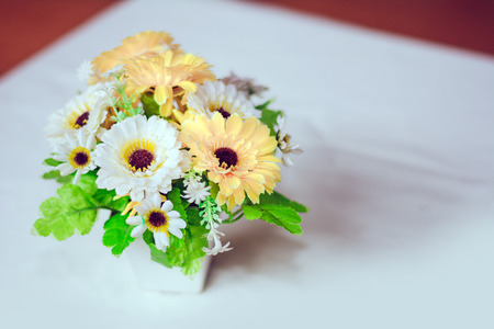 Plastic flowers with vases on the table with white cloth as the floor.