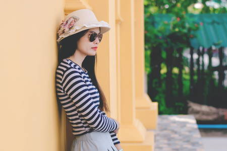 Close up shot of stylish young woman in sunglasses and hat against Yellow building background. Beautiful female model with copy space. 免版税图像