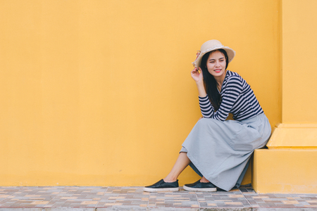 Young woman with hat,sitting next to the building against yellow background. Beautiful female model.