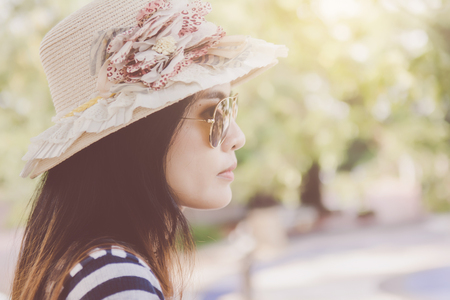 Close up shot of stylish young woman in sunglasses and hat against street background. Beautiful female model with copy space.