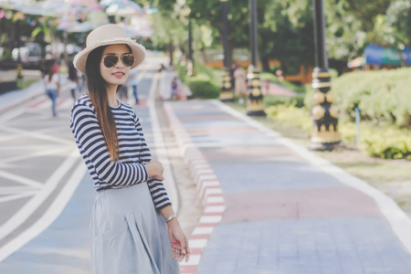 Close up shot of stylish young woman in sunglasses   and hat against  street background. Beautiful female model.