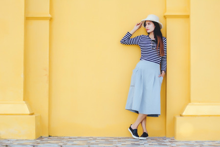 Young woman with hat,stand beside building against yellow background. Beautiful female model.
