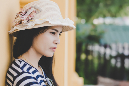 Close up shot of stylish young woman in hat against Yellow building background. Beautiful female model.