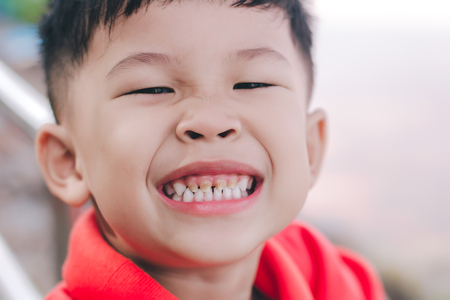 Close-up of happy kid is smiling enjoying life. Portrait of kid in nature, park or outdoors. Concept of happy family or successful. 免版税图像