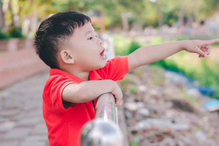 Kid boy pointing with finger  to the river,in a shocking mood.