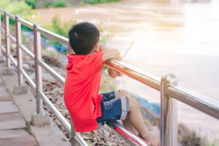 Kid boy sit on the iron balcony,looking the river. 免版税图像