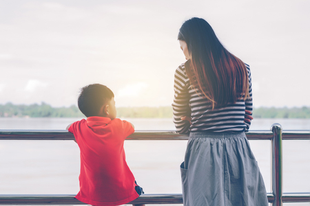 Mom and son stand on the balcony looking at the river,In sad mood. 免版税图像