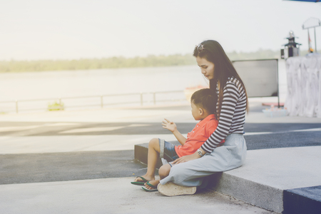 Mom and son sit on the ground near the balcony at the river,In sad mood. 免版税图像
