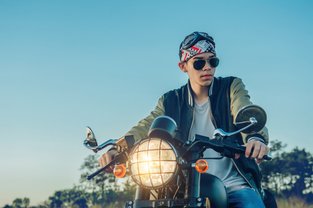 Biker man with motorcycle on street, enjoying freedom and active lifestyle, having fun on a bikers tour on sunset background.