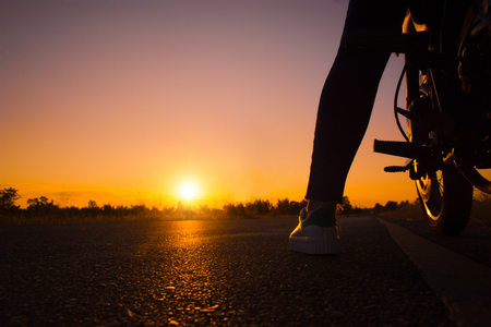 Silhouette of young woman drive with motorcycle on street, enjoying freedom and active lifestyle, having fun on a bikers tour on sunset background.