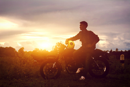 Silhouette of biker man and motorcycle with sunrise background, Rider moto trip on the street at the riverside, enjoying freedom and active lifestyle.