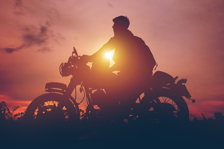 Silhouette of biker man  with his motorbike,he shoulder backpack. beside the natural lake and beautiful, enjoying freedom and active lifestyle, having fun on a bikers tour.sunset background and sky. 免版税图像