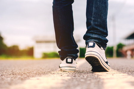 Men jeans and sneaker shoes on the road. 免版税图像