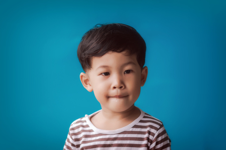 Close-up of kid against blue background. 免版税图像