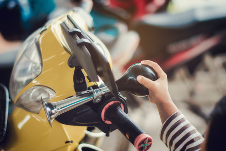 Child hand pressing horn button on motorcycle. 免版税图像