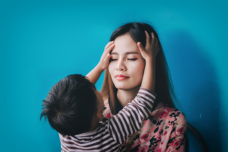 Child play with mom on against blue background.