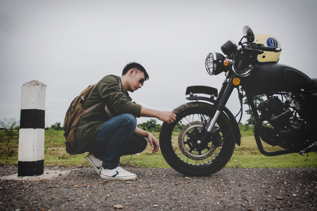 Biker man with his motorbike(motorcycle) on street and beautiful.Check Motorcycle tire inflated for safety before travel. Enjoying freedom and active lifestyle, having fun on a bikers tour. 免版税图像