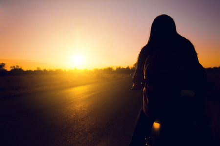 Silhouette of biker woman  with his motorbike(motorcycle ) on street,he shoulder backpack, enjoying freedom and active lifestyle, having fun on a bikers tour sunset background.