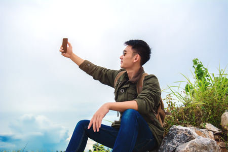 Young man using smartphone. man holding mobile smartphone using app texting sms message,wearing jacket jean,wearing black sunglasses on mountain nature background. 免版税图像 - 107501050