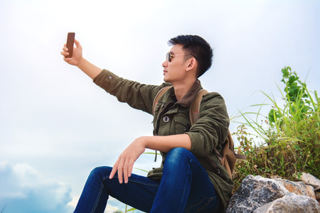 Young man using smartphone. man holding mobile smartphone using app texting sms message,wearing jacket jean,wearing black sunglasses on mountain nature background. 免版税图像