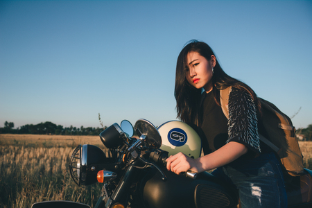 Young sexy woman on a motorcycle in nature on the sunset.Travel Concept. 免版税图像 - 124959591