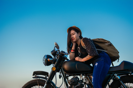 Young sexy woman on a motorcycle in nature on the sunset.Travel Concept. 免版税图像 - 124961720