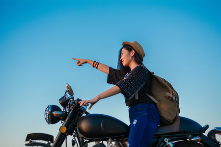 Young sexy woman on a motorcycle in nature on the sunset.Travel Concept. 免版税图像