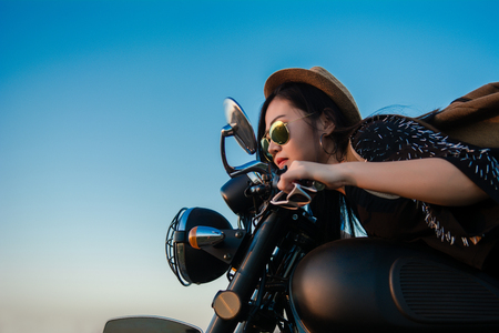 Young sexy woman on a motorcycle in nature on the sunset.Travel Concept. 免版税图像 - 124962515