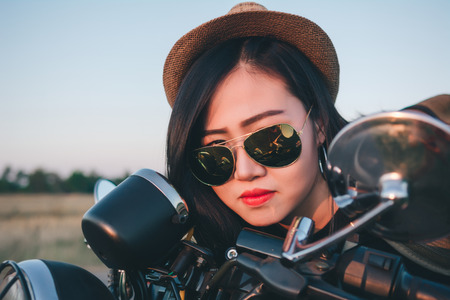 Young sexy woman on a motorcycle in nature on the sunset.Travel Concept. 免版税图像 - 124962522