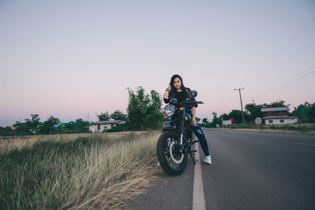 Young sexy woman on a motorcycle in nature on the sunset.Travel Concept. 免版税图像 - 124964530