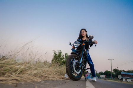 Young sexy woman on a motorcycle in nature on the sunset.Travel Concept. 免版税图像 - 124964531