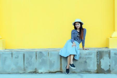 Sunny lifestyle fashion portrait of young stylish hipster woman beside building against yellow background, wearing trendy outfit, hat, travel concept. 免版税图像 - 124964544