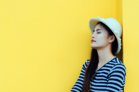 Sunny lifestyle fashion portrait of young stylish hipster woman beside building against yellow background, wearing trendy outfit, hat, travel concept. 免版税图像