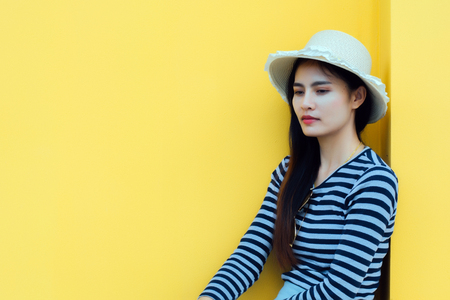 Sunny lifestyle fashion portrait of young stylish hipster woman beside building against yellow background, wearing trendy outfit, hat, travel concept. 免版税图像 - 124964546